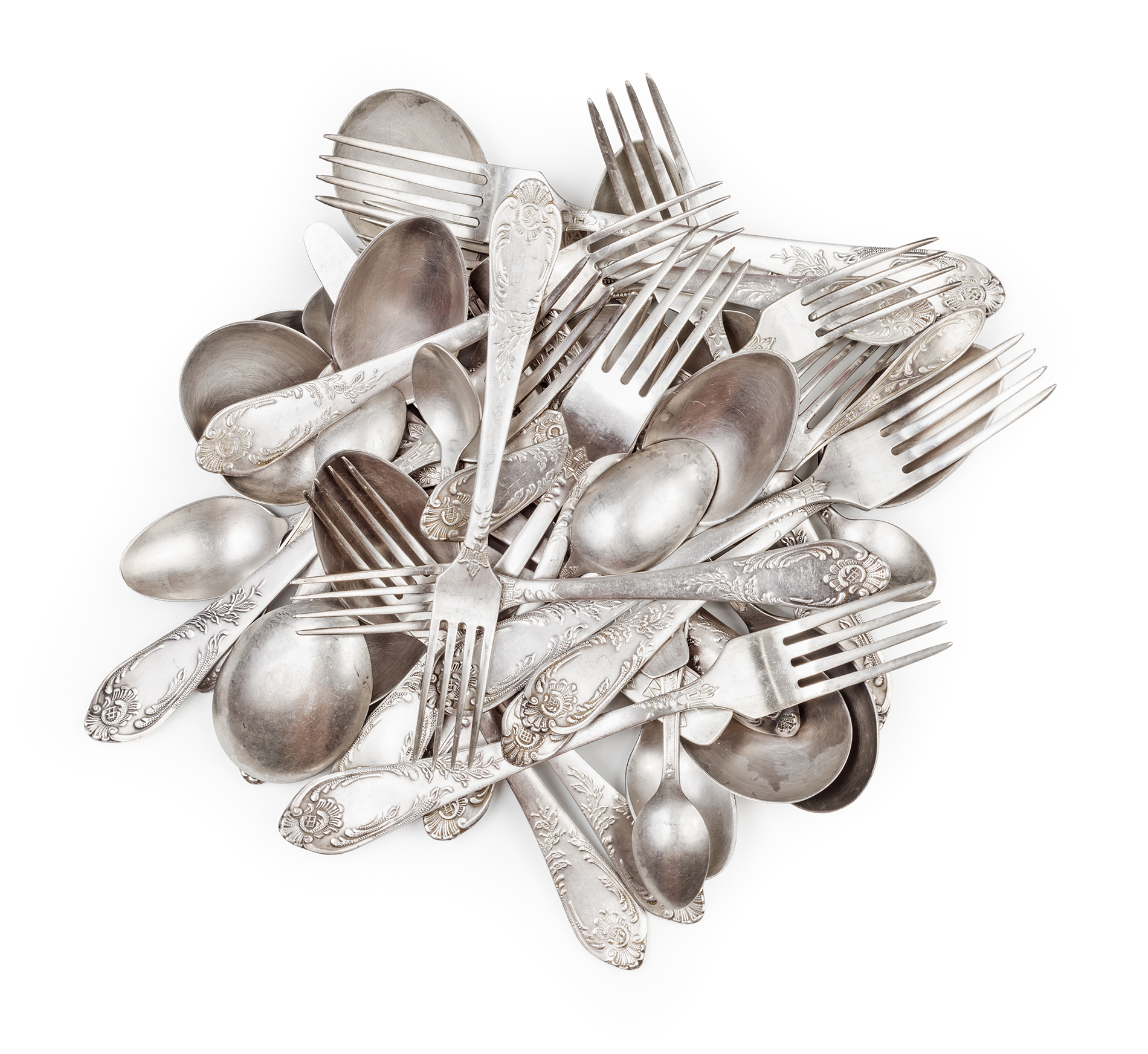 a messy pile of silver cutlery including forks, knives and spoons